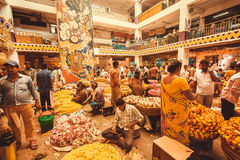 Flowers traders selling colorful floral garlands inside crowded city market Stock Photo