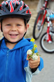 Flowers from a trip. Four year old boy on a cycle trip with father showing some wildflowers. Shallow DOF with focus on hand with flowers Stock Photo