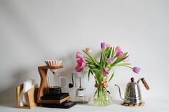 Flowers tulips bouquet in coffee decanter on white table. Manual brewing with origami dripper, paper filter stock images