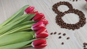 Flowers - tulips, gift, numeral eight of coffee beans on white table. stock video footage
