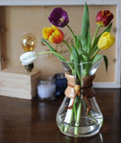 Flowers tulips in a glass container for brewing coffee as in a vase. Royalty Free Stock Photography