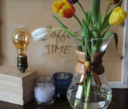 Flowers tulips in a glass container for brewing coffee as in a vase. Lamp of Edison, a wooden tray, candles in the background. Wooden table Stock Image