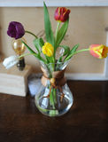 Flowers tulips in a glass container for brewing coffee as in a vase. Lamp of Edison, a wooden tray, candles in the background. Wooden table Stock Photography