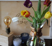 Flowers tulips in a glass container for brewing coffee as in a vase. Lamp of Edison, a wooden tray, candles in the background. Wooden table Royalty Free Stock Image