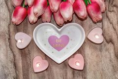 Flowers tulips, a heart-shaped plate and a heart-shaped candle. Festive background to the St. Valentine`s Day in pink colors. stock photography