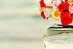 Flowers in vase. A water filled round vase and a bouquet of rose flowers Royalty Free Stock Photos