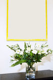 Flowers in a vase. Arrangement of flowers on white background and frame on wall royalty free stock image
