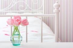 Flowers in vase in a bedroom. Royalty Free Stock Image