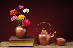 Flowers in a vase, a book and a teapot Stock Photos