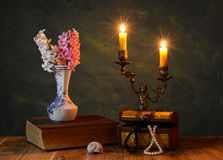 Flowers in a vase, books and candlestick Royalty Free Stock Photos
