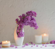 Flowers in vase with candles on background white wall. A flowers in vase with candles on background white wall Stock Images