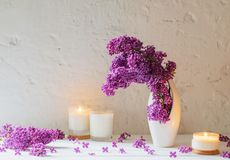Flowers in vase with candles on background white wall. The flowers in vase with candles on background white wall Stock Photo