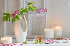Flowers in vase with candles on background white wall. Flowers in vase with candles on background old white wall Royalty Free Stock Image