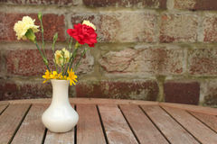 Flowers in vase. Carnations and celandines in white ceramic vase on wooden garden table with brick wall background Royalty Free Stock Photo