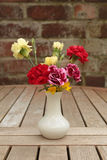 Flowers in vase. Carnations and celandines in white ceramic vase on wooden garden table with brick wall background Royalty Free Stock Image
