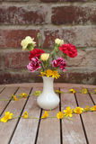 Flowers in vase with chain of celandines. Carnations and celandines in white ceramic vase on wooden garden table with brick wall background and chain of Royalty Free Stock Image