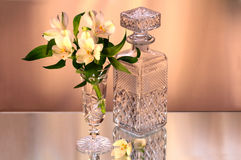 Flowers in the vase and the crystal bottle Royalty Free Stock Photos