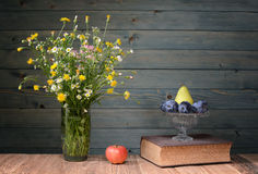 Flowers in a vase made of glass, books and fruit Royalty Free Stock Images