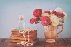 flowers in the vase next to old books, pearls necklace and perfume bottle Royalty Free Stock Image
