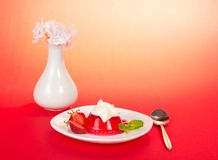 Flowers in vase, a plate with jelly and cream Stock Images