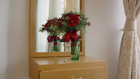 Flowers in a vase standing on a dressing table with mirror stock footage