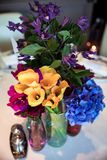 Flowers in vase on table. Yellow callas, violets and pansies stand in vase on table with white tablecloth next to salt and pepper shaker Royalty Free Stock Photos