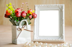 Flowers vase and vintage white picture frame. Stock Photography