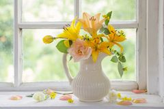 Flowers in vase on windowsill Stock Photography