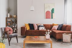 Flowers in vase on wooden coffee table in fashionable living room interior with brown corner sofa with pillows and abstract