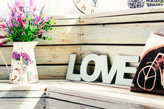 Flowers in a vase with the word Love with a pillow with a picture of a bicycle on the background of wooden boards Stock Photo