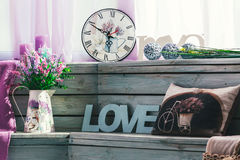 Flowers in a vase with the word Love with a pillow with a picture of a bicycle on the background of wooden boards Royalty Free Stock Image