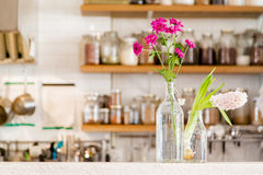 Flowers in vases in a white kitchen with wooden shelves stocked with spices. Flowers in two vases in a white kitchen with wooden shelves stocked with spices Royalty Free Stock Images