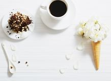 Flowers in waffle cone and chocolate cake. On white wooden background Stock Photos