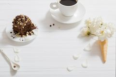 Flowers in waffle cone and chocolate cake on wooden backg. Flowers in waffle cone and chocolate cake on white wooden background royalty free stock photo