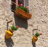 Flowers on the wall. Building wall with window and flowers in pots Stock Images