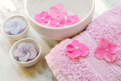 Flowers in a water bowl with a candle and a towel. Flowers in a water bowl with a candle and a wooden pestle for aromatheraphy and spa Royalty Free Stock Image