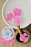 Flowers in a water bowl with a candle and a wooden pestle. For aromatheraphy and spa Royalty Free Stock Photography