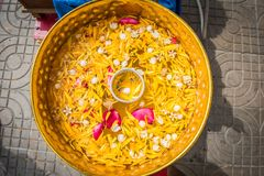 Flowers in the water bowl with the pouring Buddha On Songkran fe. Stival in Thailand stock image