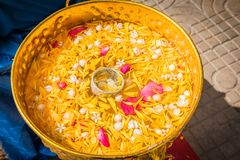 Flowers in the water bowl with the pouring Buddha On Songkran fe. Stival in Thailand royalty free stock photography