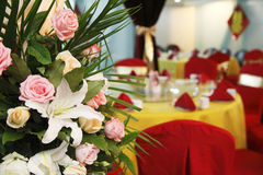 Flowers on wedding banquet. Flowers on the Chinese-style wedding banquet. Chinese characters on the wall are the double happiness royalty free stock photo