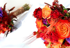 Flowers on a wedding dress. Red and orange flower bouquet on a wedding dress Stock Images