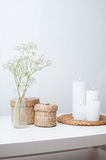 Flowers, white candles and two closed baskets Stock Images