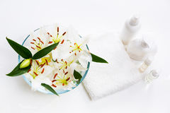 Flowers of white lilies in a round bowl with towel. And bottles Stock Image