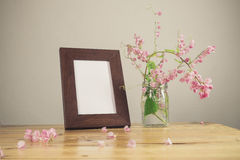 Flowers and white photo frame on wooden table Royalty Free Stock Images
