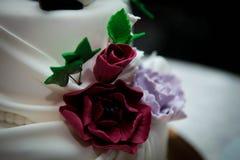 Flowers on white wedding cake Stock Photography