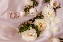 Flowers white wild rose and Golden wedding rings on white pearl color fabric Royalty Free Stock Photos