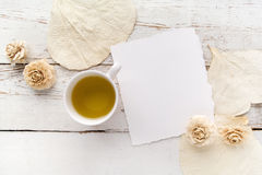 Flowers on white wooden table with blank pages and cup of green tea. Free space for text. Top view Stock Photos
