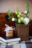 Flowers in a wicker basket, cookies, book Stock Photo