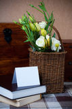 Flowers in a wicker basket, and greeting card. Yellow flowers in a wicker basket, and greeting card on the background of a wooden surface stock photography