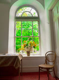 Flowers in window. Flowers in a beautiful arched window interior with green trees in background Royalty Free Stock Photo